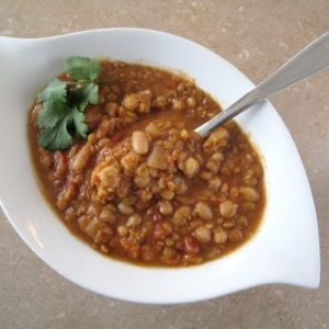 Spicy Bean & Lentil Soup in a White Bowl with Spoon in it