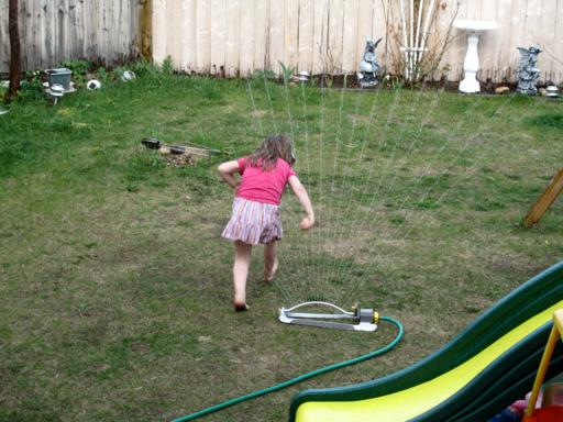 little girl stepping on the water from hose in the lawn