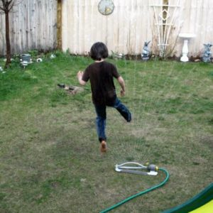 young boy playing on the water from hose in the lawn