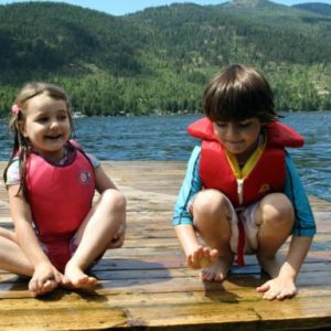 kids wearing red life jackets sitting in the wood ramp in the lake