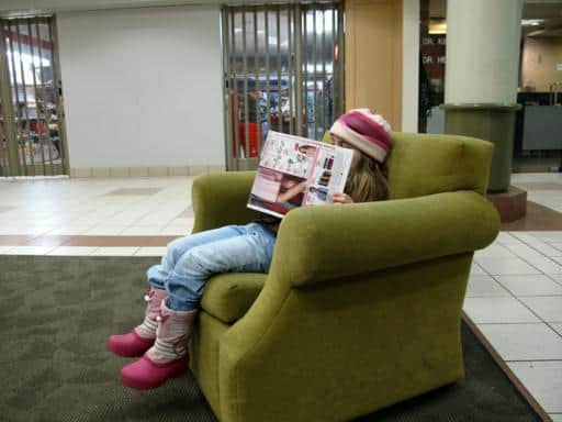 little girl sitting in the couch, reading magazine