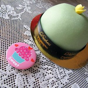 pink button and little green cake on top of table
