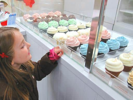 little girl in front of the display cupcakes in the store
