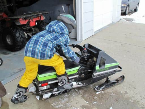 little boy learning to start his mini skidoo