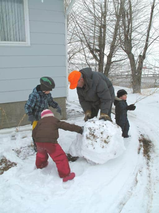 kids building up a snowman with grandfather