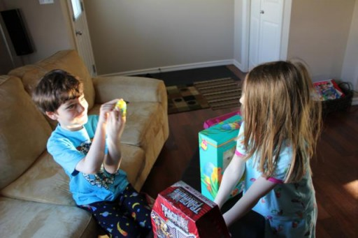 two kids playing inside the house with their new toys