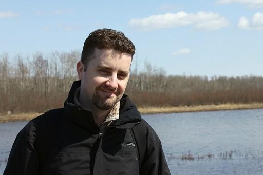 man wearing black jacket, smiling on something