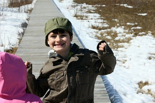 a boy smiling and showing happiness with the wooden pathway at his background