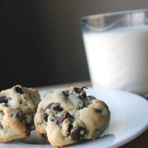 thick chewy chocolate chip cookies in a plate and a glass of milk on background