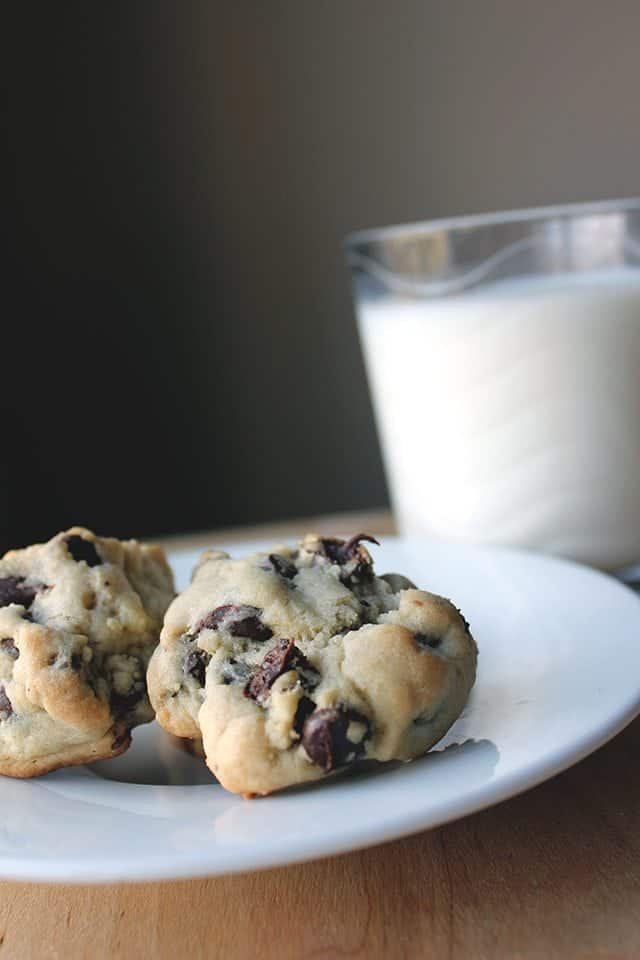 Thick & Chewy Chocolate Chip Cookies in a White plate with a Glass of milk beside it