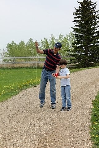 a kid being teach by a man on how to fly a kite