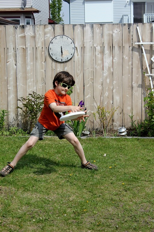 kid in orange shirt playing catching the frisbee