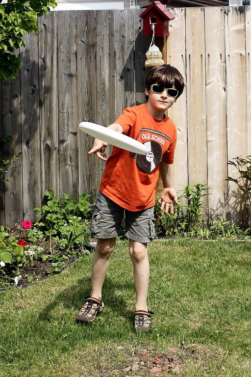 kid in orange shirt throwing a frisbee