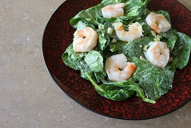 red rose designed plate with greens and dressing topped with steaming hot shrimp