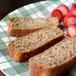 3 slices of Buttermilk Banana Bread in a green checkered plate with some fresh strawberries