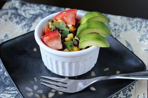 close up of Avocado, Black Bean & Corn Salad in white ramekins on a black plate with fork on side