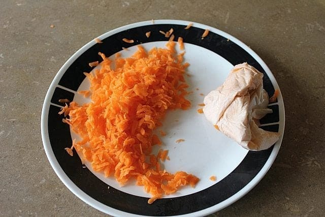 a plate with shredded carrots and a paper towel used for blotting