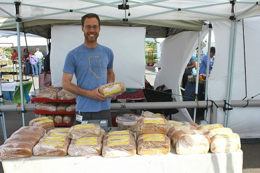 man holding a packed loaf of cinnamon raisin bread, standing in their booth