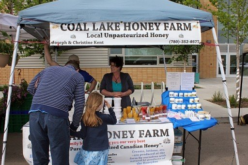 Dad and little daughter at the Coal Lake Honey Farm booth