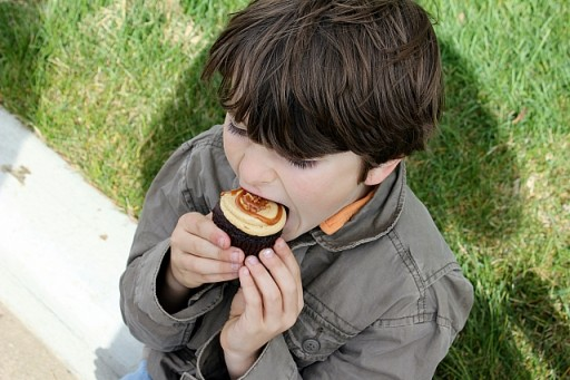 close up of little boy taking a bite of his cupcake