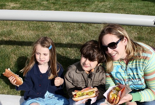 two kids with their Mom holding hotdog sandwiches