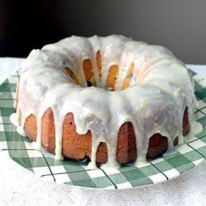 Close up of Greek Yogurt Blueberry Lemon Bundt with Lemon Icing Glaze placed on a green checkered plate
