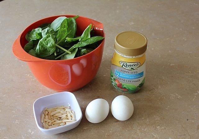 baby spinach in red bowl, 2 hard boiled eggs, almond slivers in white cup and a bottle of Poppyseed Dressing