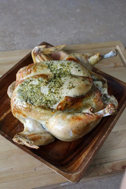 whole lemon cilantro roast chicken in a wooden tray