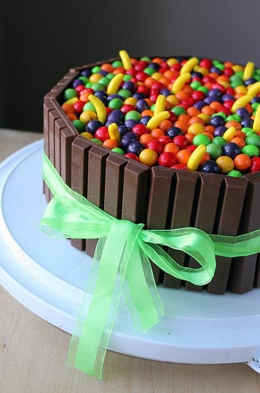 close up of Willy Wonka colorful Cake with KitKat bars and green ribbon