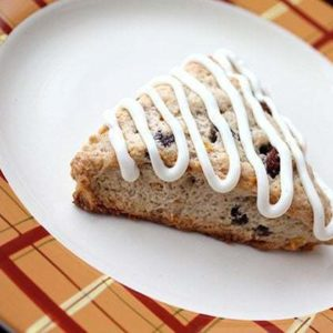 a slice of Simple Carrot Cake Scones in a white plate, drizzled with tangy cream cheese icing