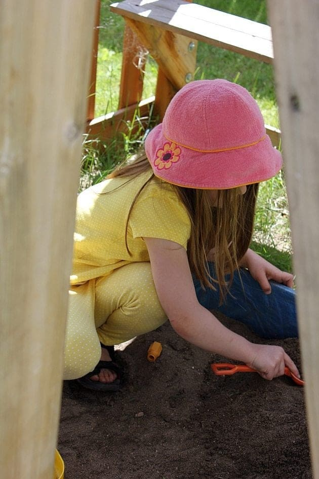 little girl wearing yellow clothes and pink cap playing in the sandbox near the fence