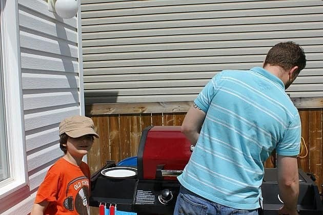 Dad lighting the fires of BBQ machine with a little boy on his side