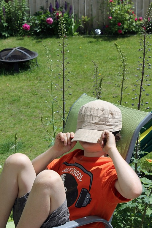 little boy covering his face with his cap while sitting in a camping chair
