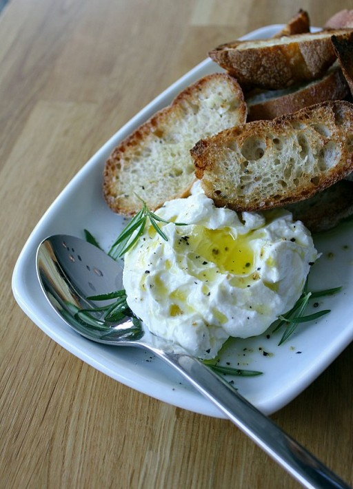 a serving of goat ricotta, maldon sea salt and crostini with a spoon on side