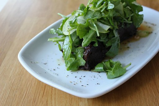 fried short rib topped with aBartlett pear salad in a white plate