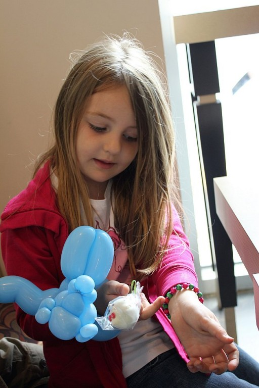 little girl with a dollar bracelet, a twoonie cake pop and a balloon animal