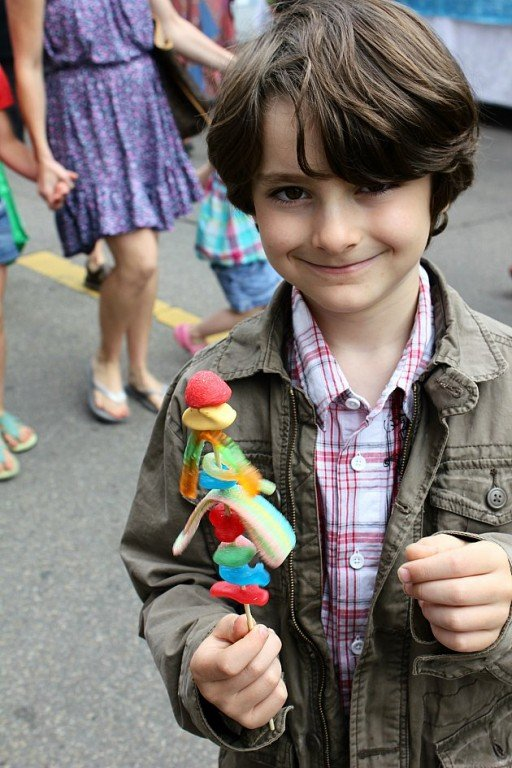 little boy smiling while holding his stick of candies