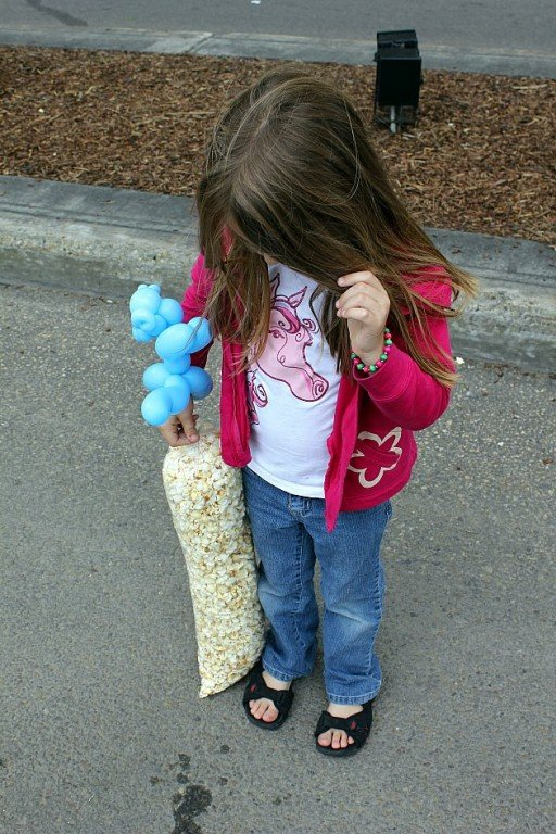 little girl looking at her bag of kettle corn