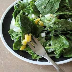 Egg, Almond & Spinach Salad in a bowl with a fork in it