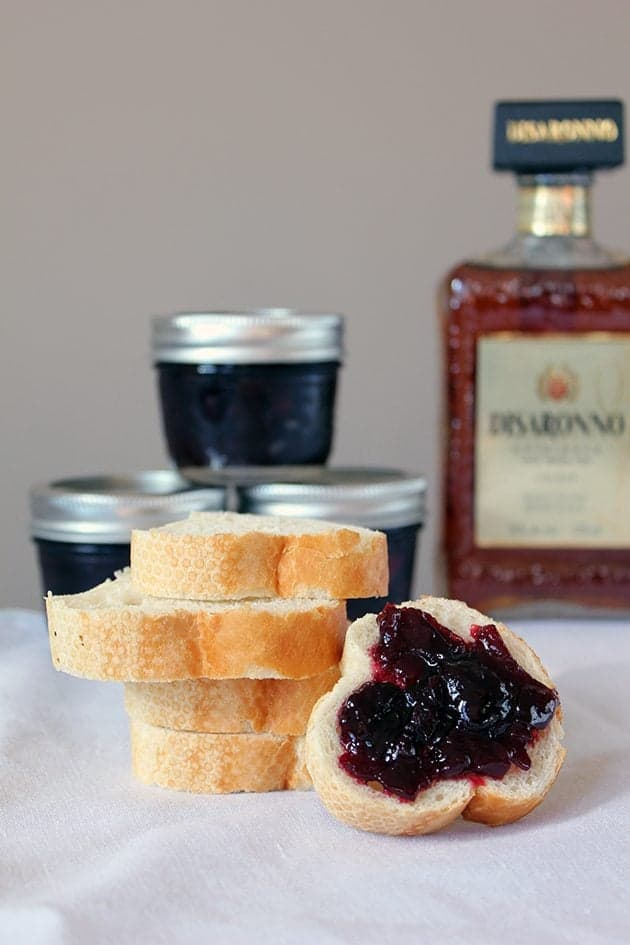 A stack of toast bread slices, one with boozy sweet cherry preserves spread over it. Small jar containers with cherry preserved on the background.