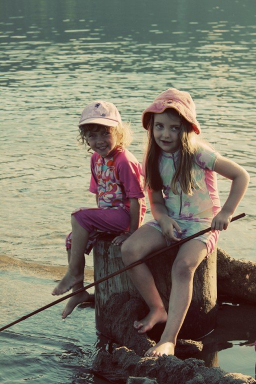 two young girls just sitting in a wood log, holding a stick and playing with water