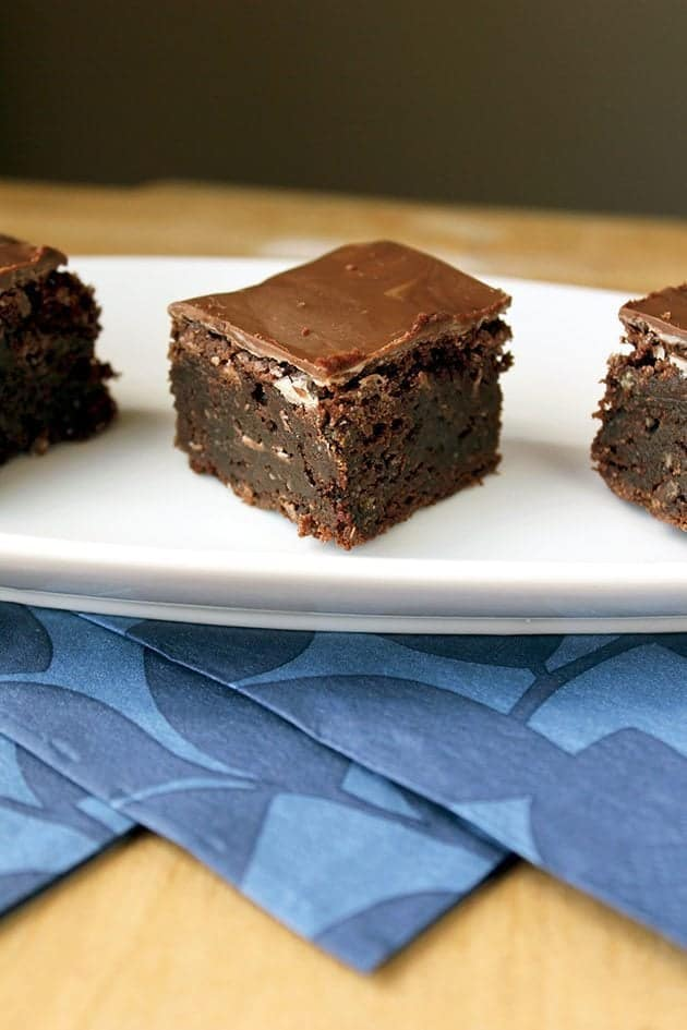 brownies with Creme de Menthe chips on top placed on white plate