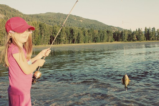 little girl caught a fish with her fishing rod