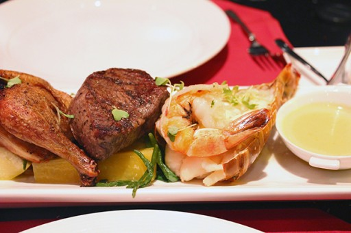 gigantic prawn and half a Cornish game hen served on potatoes and vegetables