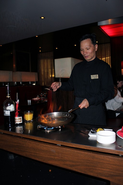 a chef in black uniform cooking