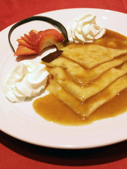 Crepe Suzette - crepes with a sauce of caramelized sugar and butter, with slices of strawberries and whipped cream on side