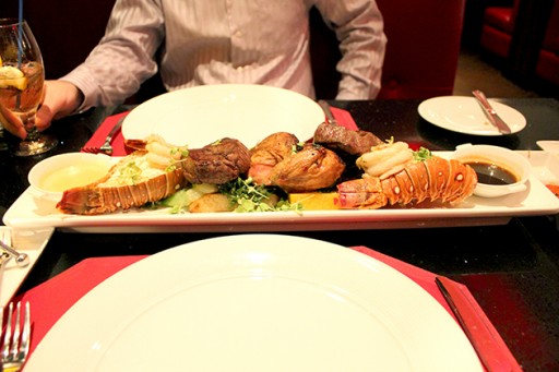 Two lobster tails, two filet mignon, two gigantic prawns and half a Cornish game hen served on potatoes and vegetables