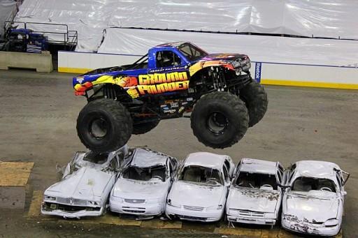 monster truck driving over cars