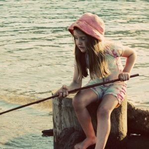 little girl sitting in an old wood log in the lake holding a long stick