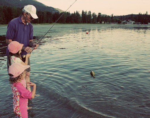 grandfather wearing a white cap do fishing together with two little girls in the lake